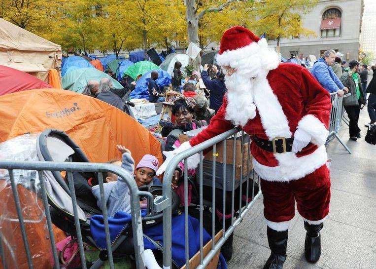 De kerstman bracht maandag een bezoek aan kinderen in Zuccotti Park, waar het kampement van de New Yorkse Occupy-beweging is opgesteld. Beeld afp