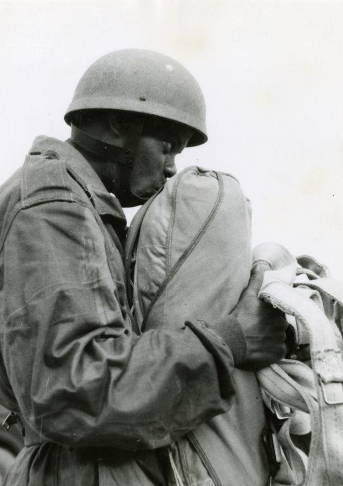 De Surinaamse militair Guillaume Kranenburg, parachutist bij de Prinses Irene Brigade, plakt bij wijze van traditie zijn kauwgom op de parachute om geluk te brengen