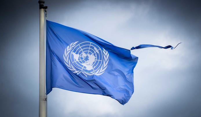 Een VN vlag wappert in de wind buiten het Vredespaleis