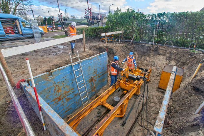 Medewerkers van aannemersbedrijf Van den Heuvel bij de installatie waarmee de nieuwe leiding onder het spoor door wordt geperst. Projectleider Rien Timmermans van Brabant Water kijkt toe.