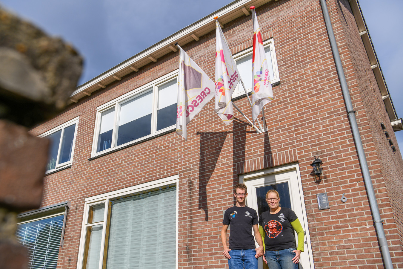 Johan en Anne Kanters, met drie vlaggen van de verschillende buurtschappen aan hun woning.