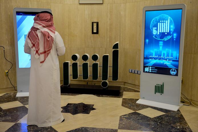 Een medewerker van het Saoedische ministerie van Binnenlandse Zaken staat voor een display met daarop het startscherm van de omstreden app Absher.