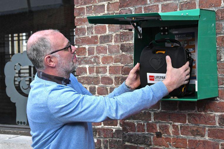 Directeur Luc Beyens hangt het toestel tegen de gevel van de turnzaal.