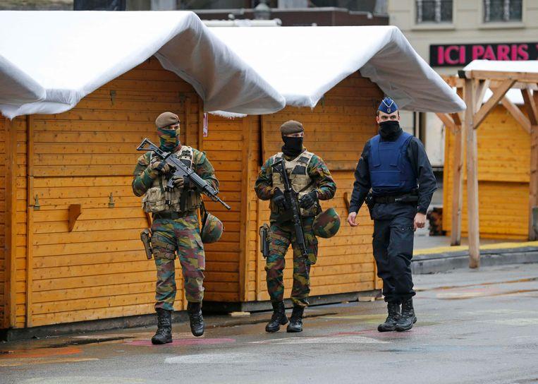 Militairen en politie patrouilleren aan gesloten kerstkraampjes in het centrum van Brussel.