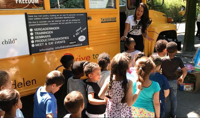 Kinderen in de rij voor de bus, daarbinnen mogen zij drie cadeautjes uitzoeken.