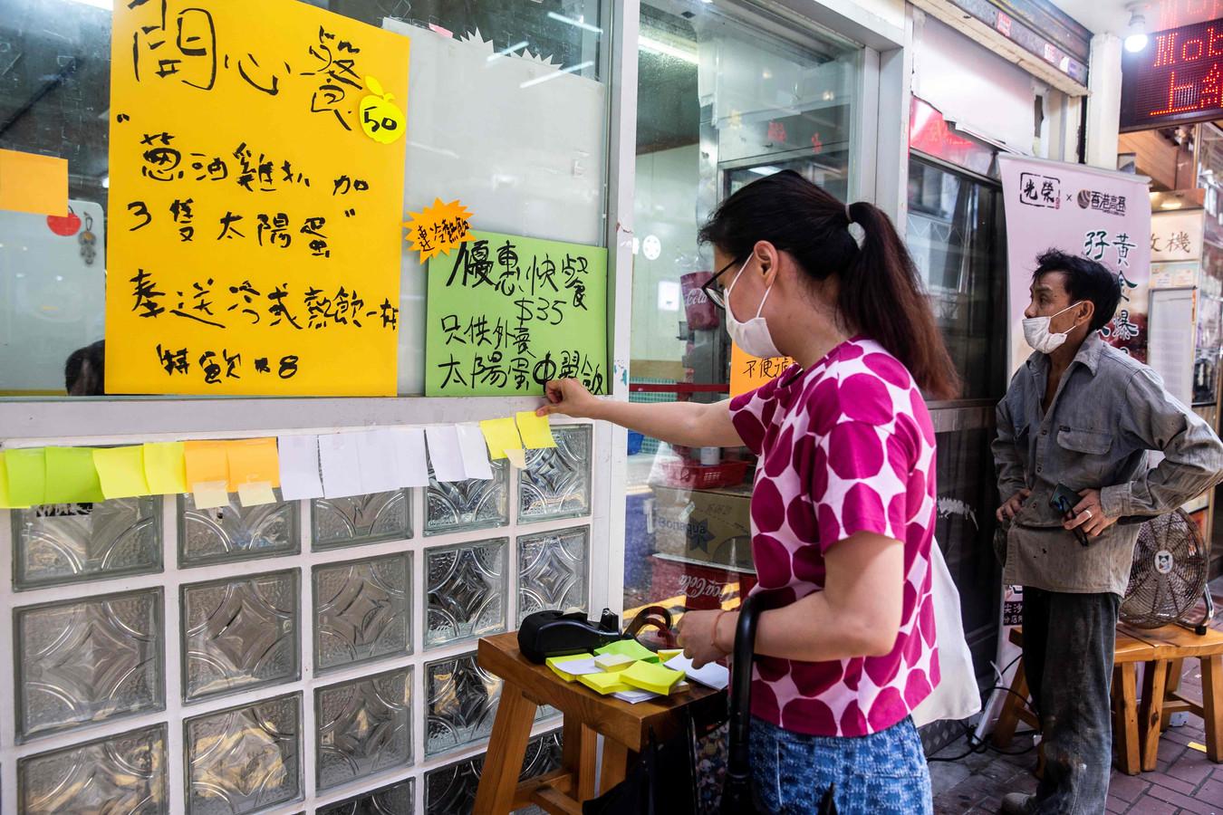 Een vrouw plakt lege briefjes op een plek die tot deze week werd gebruikt voor briefjes met teksten waarin werd gepleit voor meer vrijheid en democratie in Hongkong. De lege briefjes zijn een nieuwe vorm van protest nu de overheid activisten de mond wil snoeren met een nieuwe, strenge veiligheidswet. Alle teksten die verwijzen naar autonomie zijn verboden. Foto ISAAC LAWRENCE / AFP