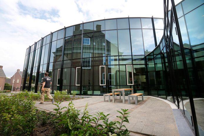Hier wordt het monumentale deel  van het gemeentehuis in Opheusden weerspiegeld  in de glazen pui van de nieuwbouw.