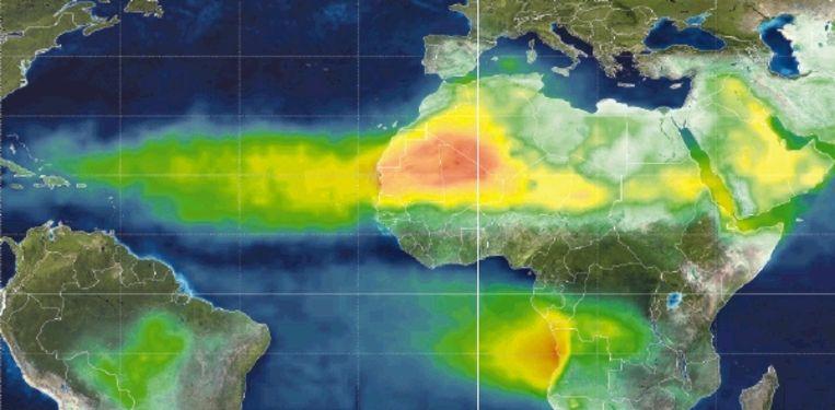 Op deze satellietopname van de Nasa is te zien hoe een stofstroom zich vanuit de Sahara en vanaf het Arabisch Schiereiland richting Midden- en Zuid-Amerika verspreidt. De stroom vanuit het westen van Zuidelijk-Afrika en Zuid-Amerika wordt vooral veroorzaakt door de verbranding van biomassa. (Trouw) Beeld Science Photo Library