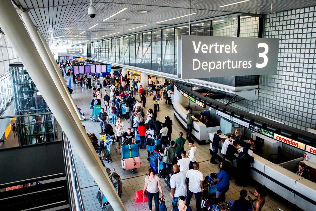Reizigers in de vertrekhal op Schiphol.