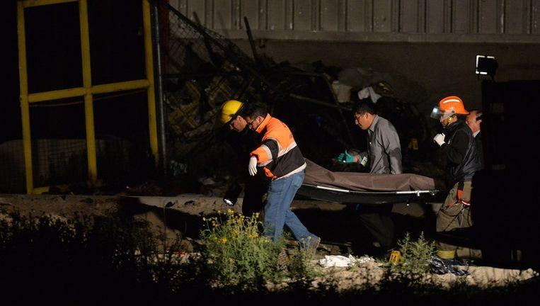 Een van de slachtoffers van de crash wordt weggedragen. Beeld epa