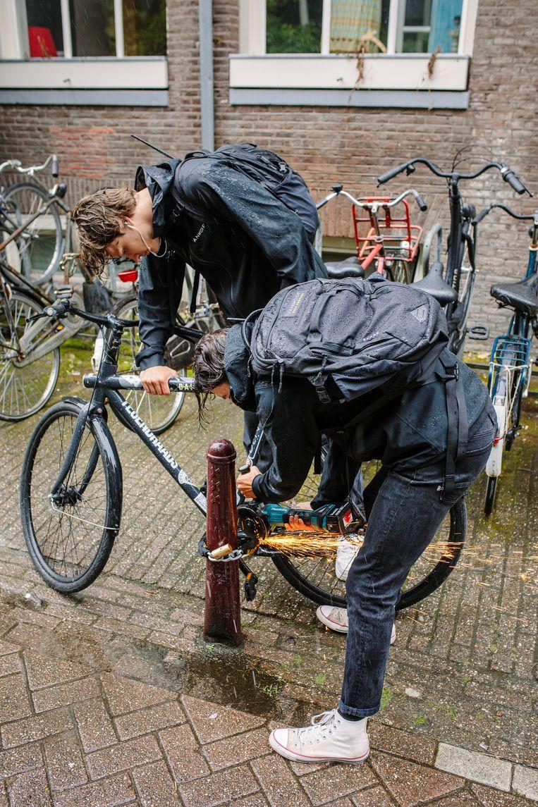 Fietsenjagers Idse Luirink (l) en Indigo Versteeg slijpen een gestolen fiets los. Beeld Marc Driessen