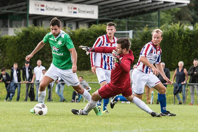 De 8-0 in de maak; Tom Janssen van Baronie omspeelt JEKA-keeper Koen Hendrickx en schuift het voorlaatste doelpunt van de middag binnen.