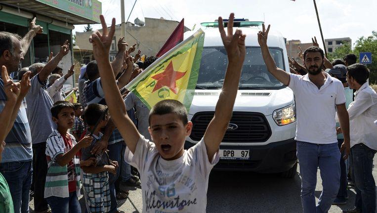 Archieffoto van inwoners van Kobani die de overleden militair Keith Broomfield gedenken. De Amerikaan stierf tijdens gevechten tegen IS. Beeld afp