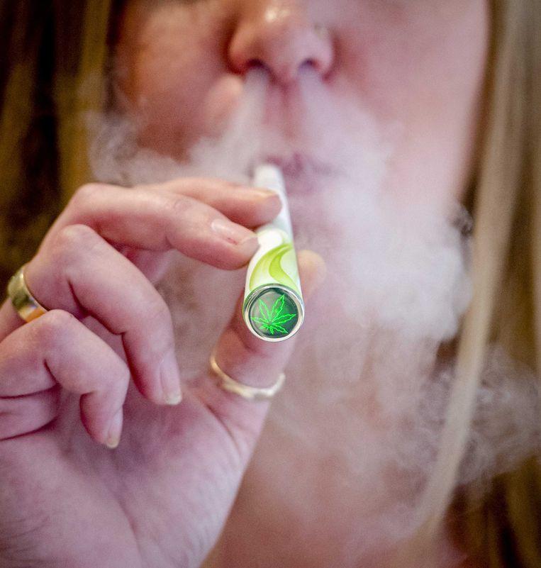 Een vrouw rookt een elektronische sigaret met cannabissmaak. Beeld ANP XTRA