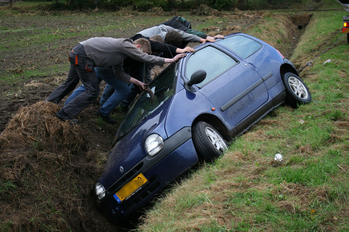 Jongens proberen de auto weer uit de sloot te krijgen.