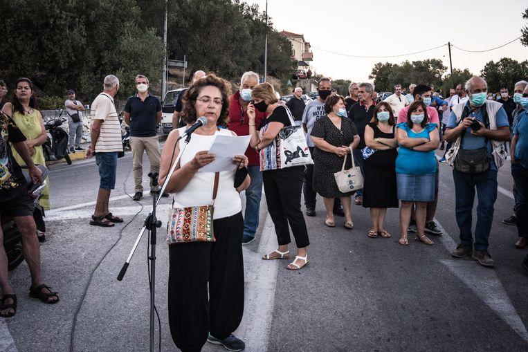 Kleoniki Chronis, voorzitter van de bewonersvereniging van het dorp Moria, spreekt de betogers toe. Beeld Nicola Zolin