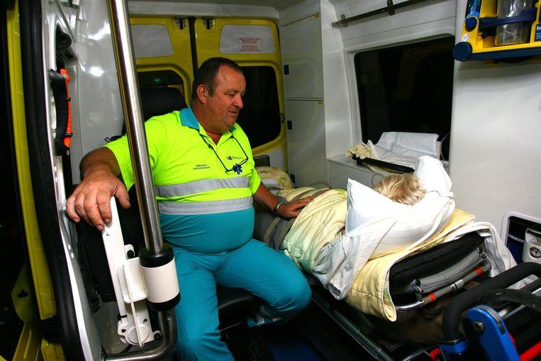 Een patiënt wordt met een ambulance verhuisd. Beeld -