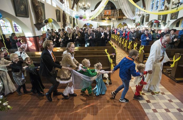 Pastor Huitink gaat voorop in de polonaise tijdens de carnavalsmis.