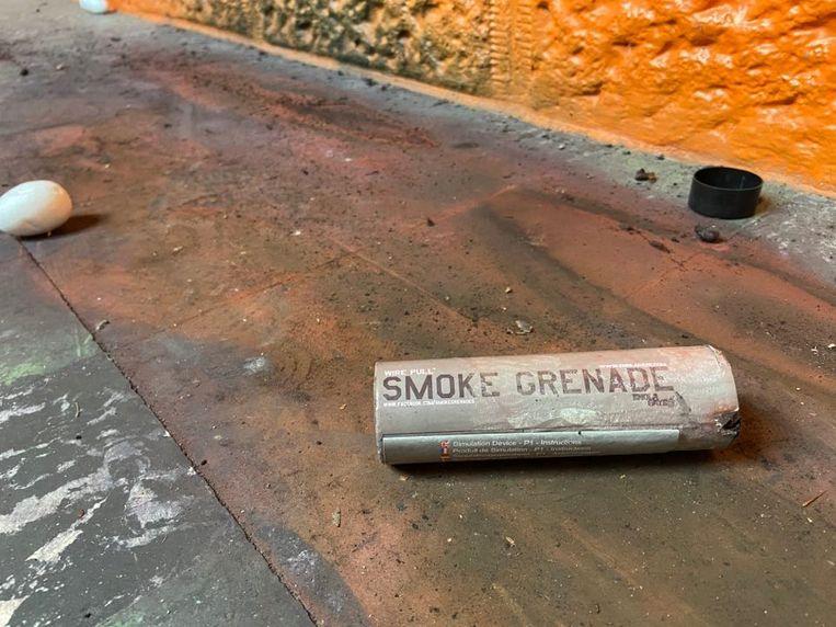 Een huls van een rookbom slingert rond.