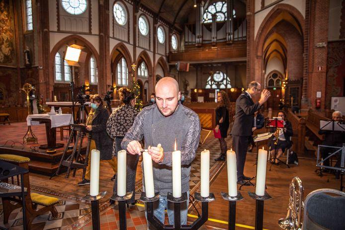 Voorganger Joshi van Veen steekt de kaarsen aan bij de opnamen van de gezamelijke kerstviering in de Maria Magdalenakerk in Goes.