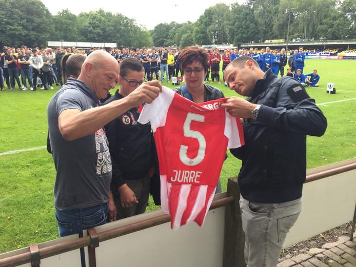 Het gezin Janssen bekijkt samen met oud-voetballer Danny Koevermans (r) het PSV shirt met de baan van hun overleden kind en broertje Jurre