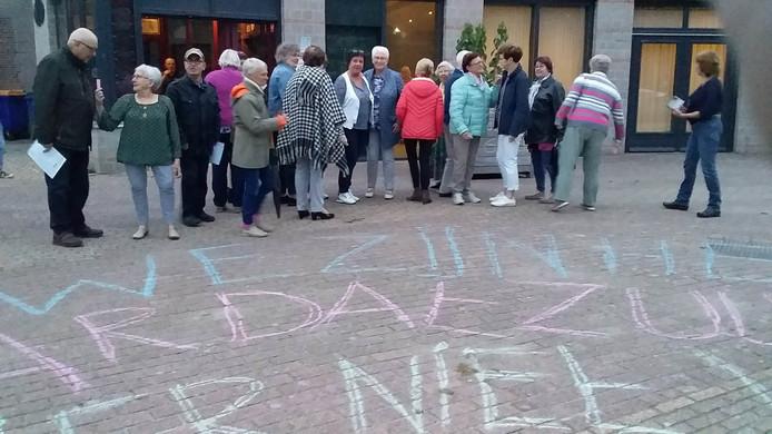 Loonse zangers en muzikanten protesteren met stoepkrijt op het Weteringplein met de tekst:  'Wij zijn het zat, maar dat zullen we hier niet worden'.