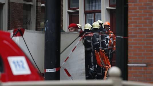 Brandweermannen gaan met een brancard het pand in waar bij een brand een man is omgekomen.