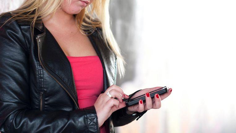 Een meisje bekijkt berichten op haar smartphone. Beeld null