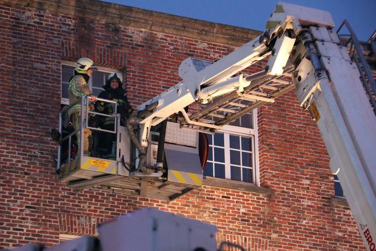 De brandweer moest met de ladderwagens mensen bevrijden die vastzaten op de bovenste verdieping.