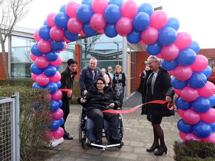 Toekomstige bewoner Claudia Oskam knipt het lint door bij de opening van de twee nieuwe groepswoningen voor jonge mensen met dementie.