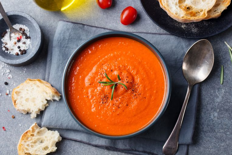 Tomato soup in a black bowl on grey stone background. Top view. Copy space