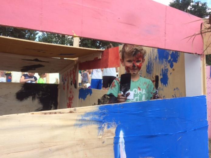 Sven van de Aa schildert zijn hut tijdens de kindervakantieweek in Zijtaart.