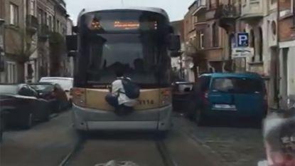 Brusselse tram is overvol, dus gaat deze jongen maar aan het tramsurfen