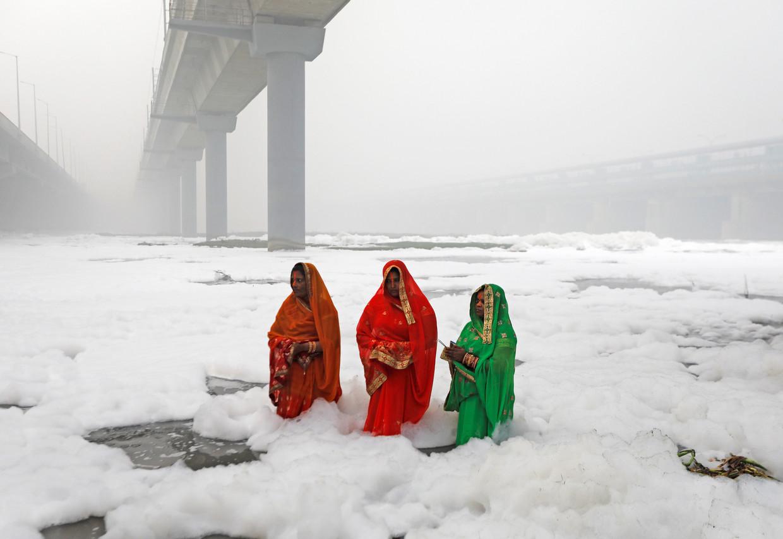 Drie Hindoestaanse vrouwen aanbidden de zon in de vervuilde wateren van de Yamuna rivier in Delhi.