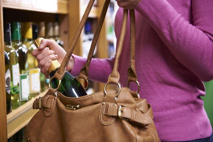Vrouw steelt een fles wijn