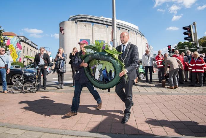 Herdenking van de evacuatie in 2017. Burgemeester Marcouch en oorlogskind Gé Bijlsma  leggen een krans bij de plaquette in een hoek aan de drukke Apeldoornsestraat tegenover bioscoop Rembrandt.