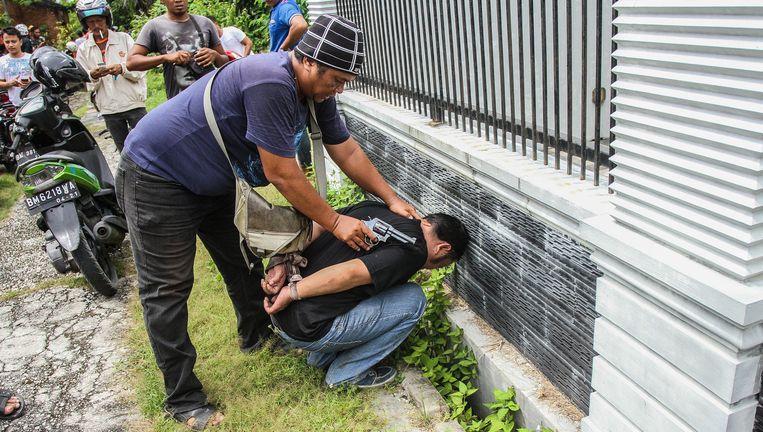 Een agent in burger arresteert een ontsnapte gevangene.