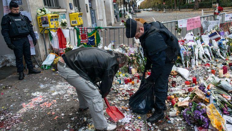 Parijs: twee mannen onder wie een politieagent halen waxinelichtjes en resten rouwmateriaal weg bij de ingang van popconcertzaal Le Bataclan, waar vrijdagavond zeker 89 mensen de dood vonden. Beeld Getty Images