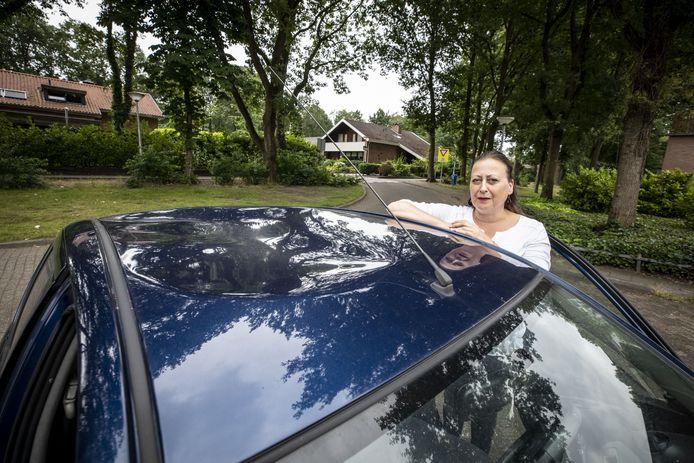 Mariëlle Rotmann bij haar Toyota Yaris met enorme deuk in het dak.