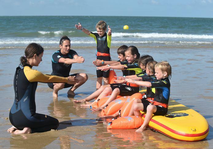 Kinderen leren zwemmen in zee.