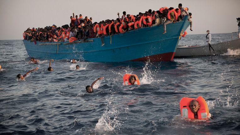 Migranten springen uit een overbevolkte boot op de Middellandse Zee terwijl ze gered worden door een ngo op 29 augustus 2016.