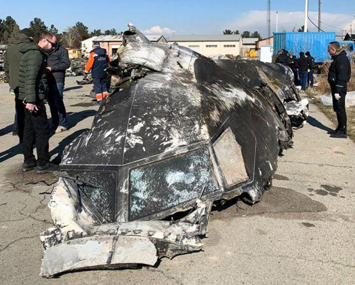 Des personnes debout en train d'analyser les fragments et les restes de l'avion Boeing 737-800 d'Ukraine International Airlines qui s'est écrasé devant la capitale iranienne, Téhéran, le 8 janvier 2020.