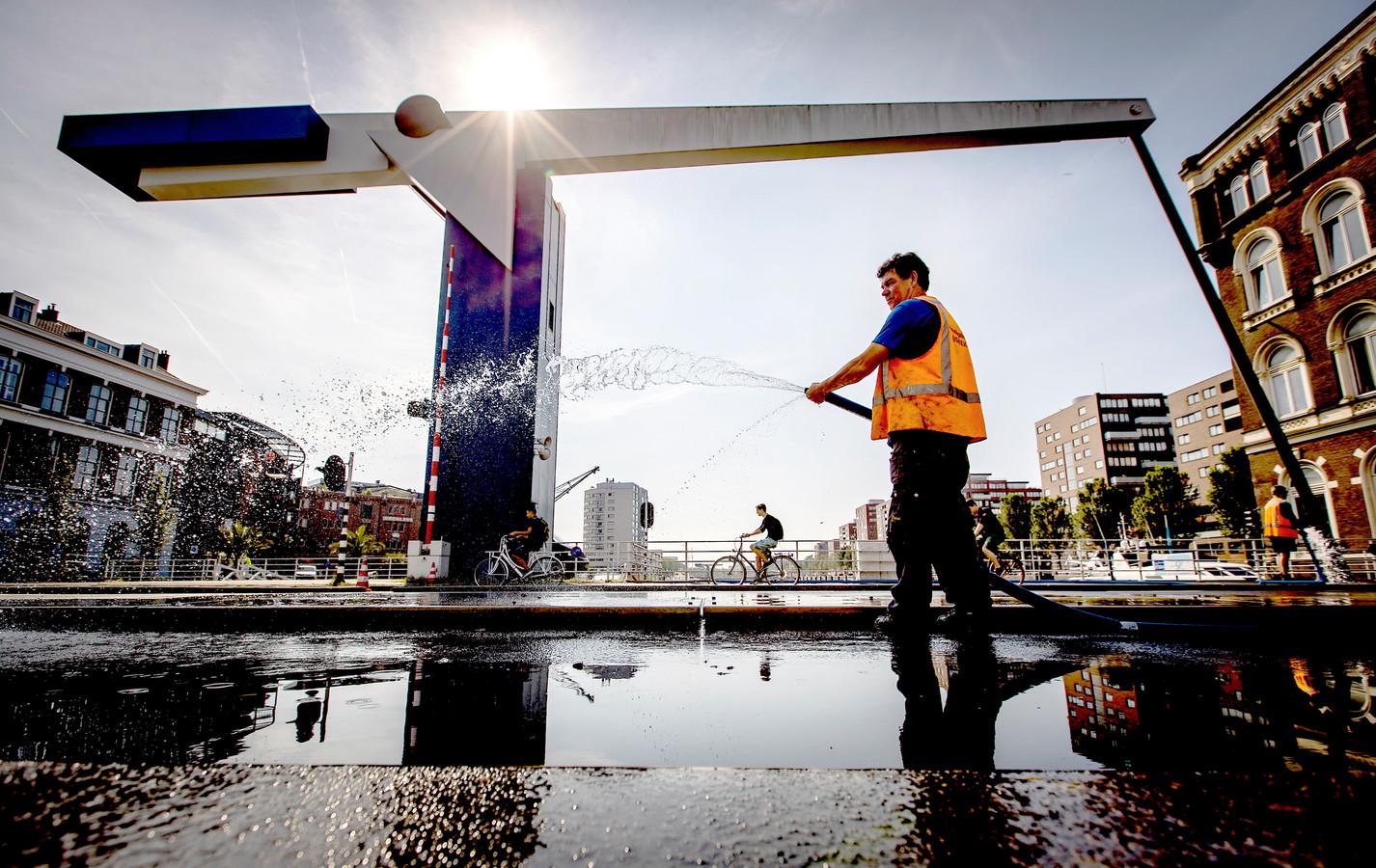 Medewerkers van de Gemeente Rotterdam houden de Binnenhavenbrug nat om storingen vanwege de hoge temperatuur te voorkomen.