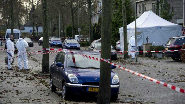Politie-medewerkers bekijken sporen na de vondst van een dode man in een auto bij een huis Diemen Beeld anp