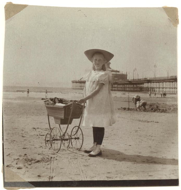 Meisje met poppenwagen op het strand. Op de achtergrond het wandelhoofd Wilhelmina. Foto dateert van circa 1905.