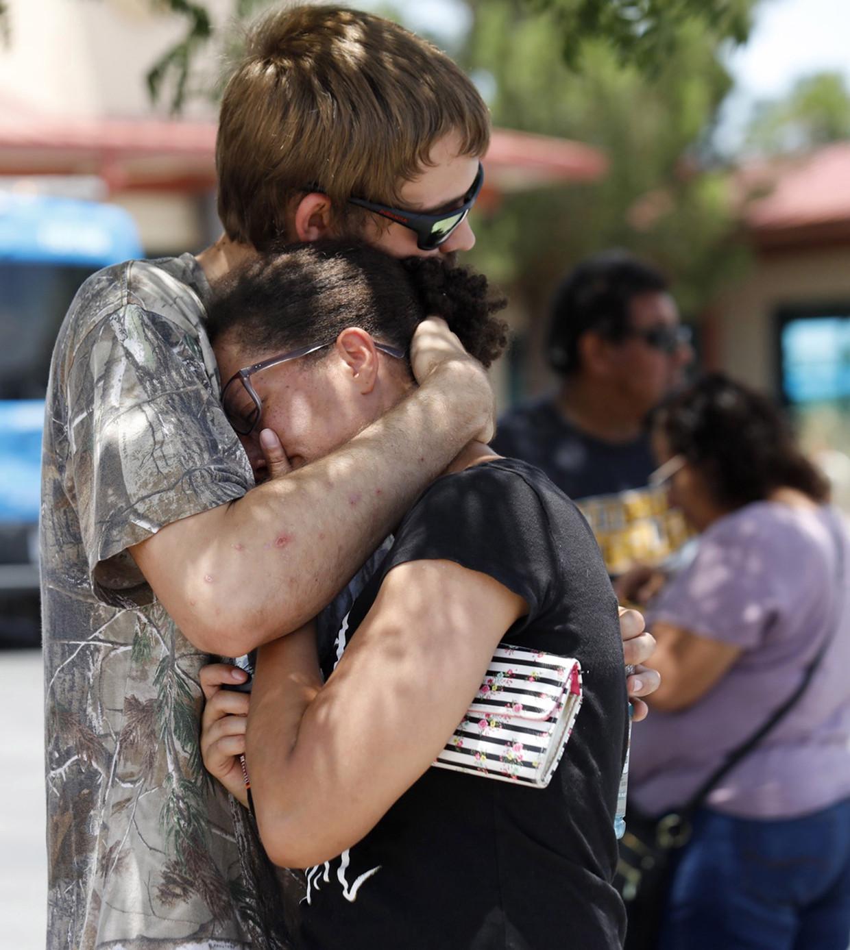 Kendall Long (L) knuffelt zijn vrouw Kianna nadat ze de schietpartij overleefden.