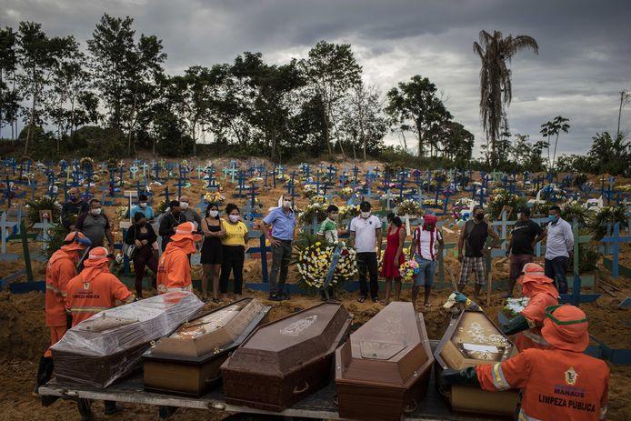 Inwoners van Manaus wonen een massabegrafenis bij.