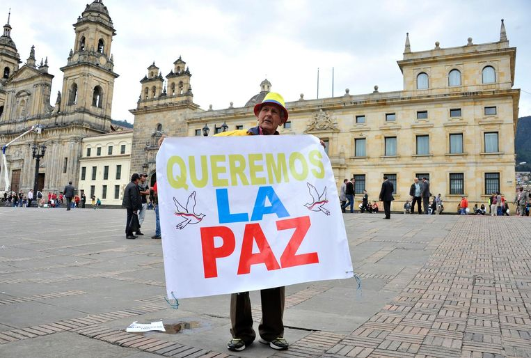 Een voorstander van het vredesakkoord houdt een spandoek omhoog met 'wij willen vrede' tijdens een demonstratie voor het Colombiaanse Senaat. Beeld afp