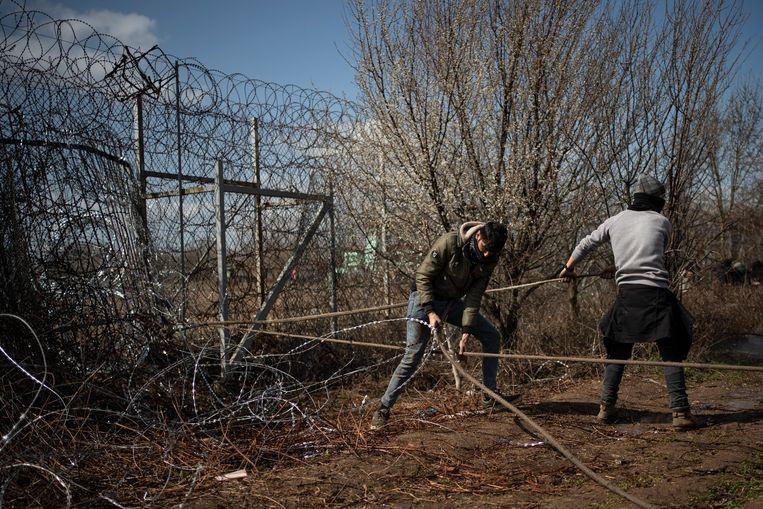 Migranten proberen het hek kapot te krijgen.