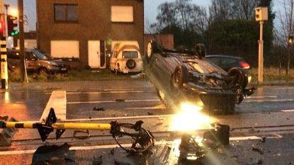 Auto ramt verkeerslicht en gaat over de kop